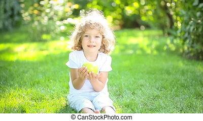 Happy child eating apple