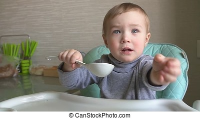 Happy child eating porridge with a big spoon