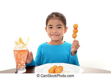 Happy child eating sweet