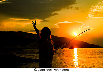 happy child fishing by the sea silhouette