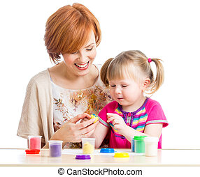 Happy child girl and mother sitting at table and playing with colorful clay toy