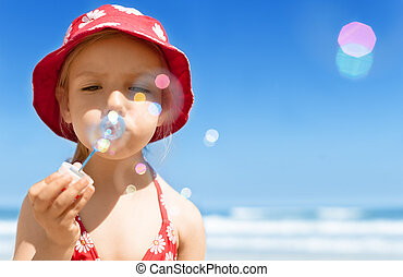 Happy child girl, blowing soap bubbles, playing, having fun on summer beach