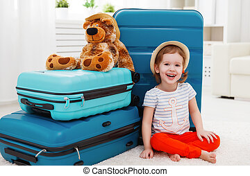 happy child girl collect the suitcase on vacation