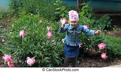 Happy Child girl dances in the garden with peonies.