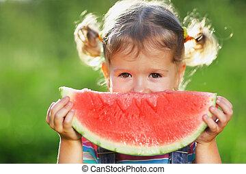 Happy child girl eats watermelon