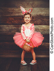 Happy child girl in costume Easter bunny rabbit with basket eggs on wooden background