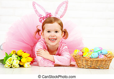 Happy child girl in  costume Easter bunny rabbit with eggs and flowers