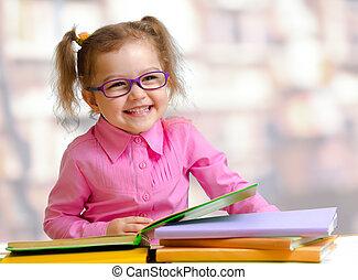 Happy child girl in eyeglasses reading books sitting at ...
