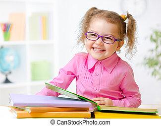 Happy child girl in glasses reading books in room - Happy...