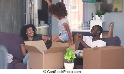 Happy child girl jump out of box play with black parents