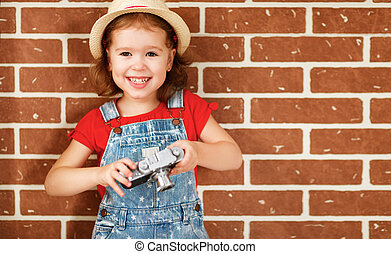 Happy child girl photographer with camera at brick wall -...