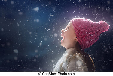 kid on dark background - Happy child girl playing on a snowy...