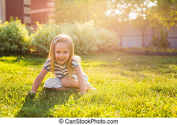 happy child girl playing on meadow in summer in nature