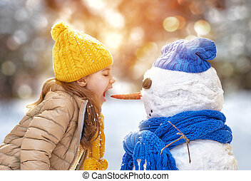 girl playing with a snowman - Happy child girl playing with...