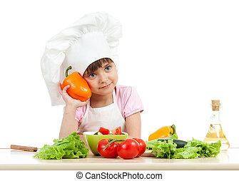 happy child girl preparing vegetarian dish