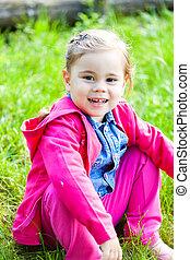 Happy child girl sitting on green grass