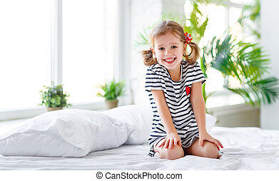 happy child girl smiling in bed