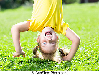 child girl standing upside down on her head on grass in summer