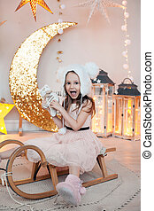 Happy child girl wearing fur hat posing on sledge against christmas decorations.