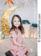 Happy child girl wearing pink dress posing against christmas decorations.