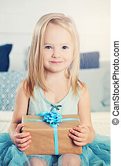 Happy Child Girl with a Gift. Beautiful Little Girl in Blue Dress