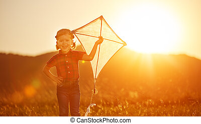 happy child girl with a kite on meadow in summer