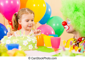 happy child girl with clown on birthday party