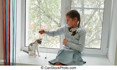 happy child girl with her cat sitting window sill at sunset. little girl is played with a pet cat white gray. girl and cat concept lifestyle