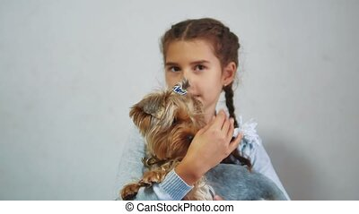 happy child girl with her dog holds on hands. little girl is...