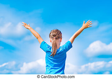 Happy child girl with open arms outdoor under blue sky. Young girl relax outdoors. Freedom concept