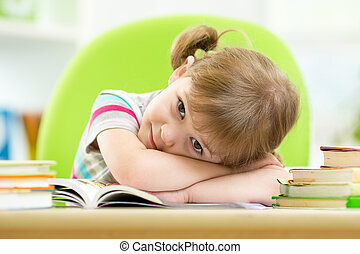 Happy child girl with stack books at table
