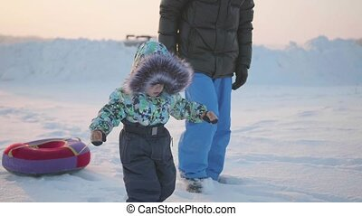 happy child goes through the snow with his father. snowy winter landscape. sports outdoors