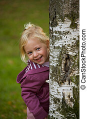 Happy child looks out from behind a tree
