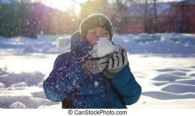 happy child having fun in winter Park on a Sunny day.Blows the snow from the palm of