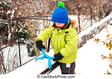 Happy child having fun on a walk in winter. Little boy playing with snowball maker.