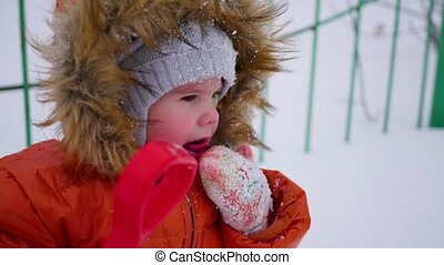 happy child having fun playing in the park on a sunny winter day. Snow winter landscape. on open air