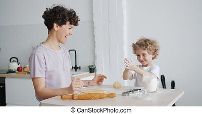 Happy child having fun with flour clapping hands cooking...