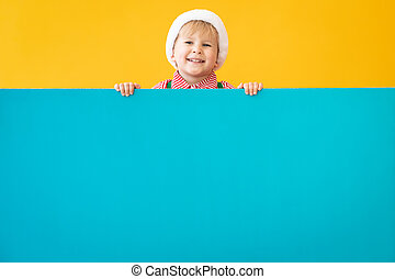 Happy child holding blue Christmas banner blank against yellow background