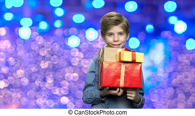 Happy child holding Christmas gift boxes. Handsome little...
