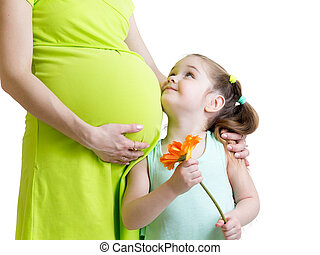 happy child holding flower looks at pregnant mother