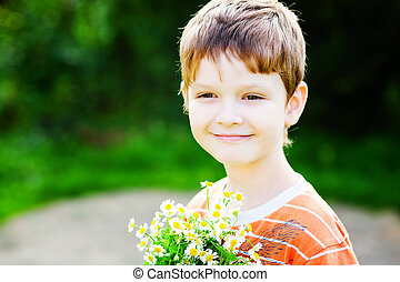 Happy child in a field with a bouquet of daisy.