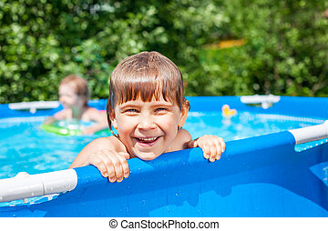 Happy child in a swimming pool outdoors