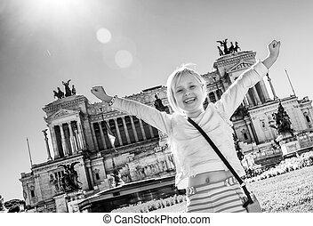 happy child in front of Palazzo Venezia in Rome, Italy rejoicing