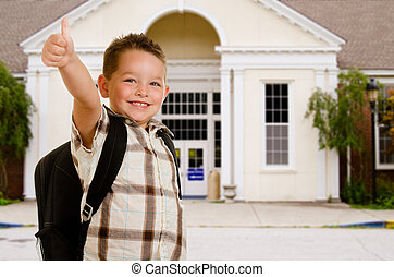 Happy child in front of school wearing back pack and giving thumbs up