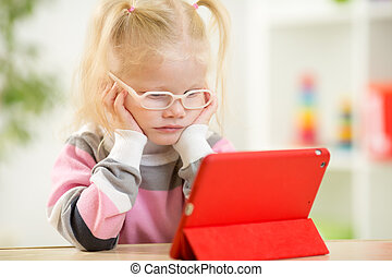 happy child in glasses looking at mini tablet pc screen...