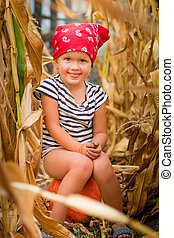 Happy child in red bandana and stripe tee showing tongue and sits on a pumpkinin the cornfield. dry corn
