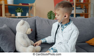 Happy child in white medical gown examining stuffed bear ...