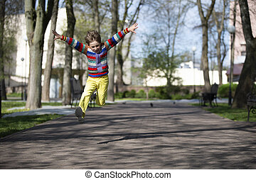Happy child is jumping up for a walk in the park.