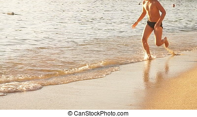 Happy Child is running on the beach at Sunset, raises splashes. Slow Motion