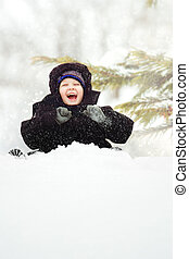 Happy child is sitting in the snow in the park.